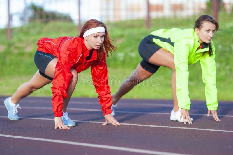 Två Caucasian idrottsman nen som står förberedda för att köra på spårkurs royaltyfri foto