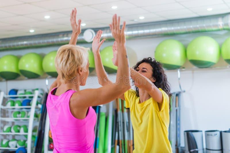 Två Caucasian kvinnor som ger höjdpunkt fem, når utbildning i idrottshall royaltyfri fotografi