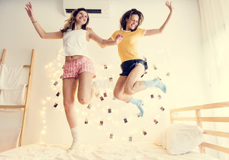 Två Caucasian kvinnor som tillsammans hoppar på sängen arkivfoto