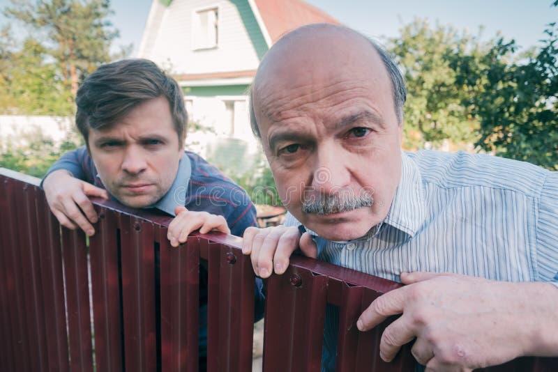 Två caucasian män som håller ögonen på försiktigt över staketet royaltyfria foton
