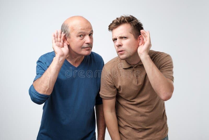 Två caucasian män som hör med handen på örat som isoleras på en vit bakgrund Please talar högt royaltyfri fotografi