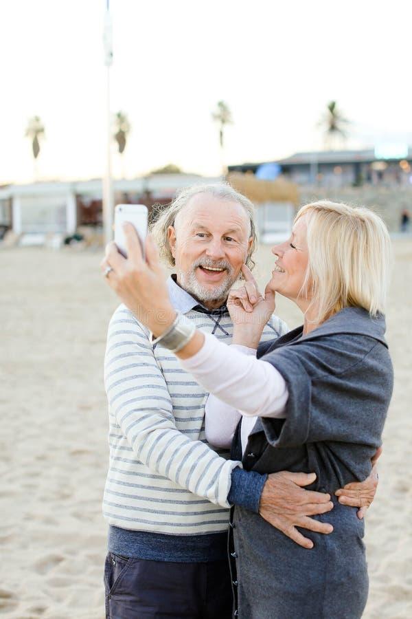 Två caucasian pensionärer som gör selfie vid smartphonen på sandstranden royaltyfria bilder
