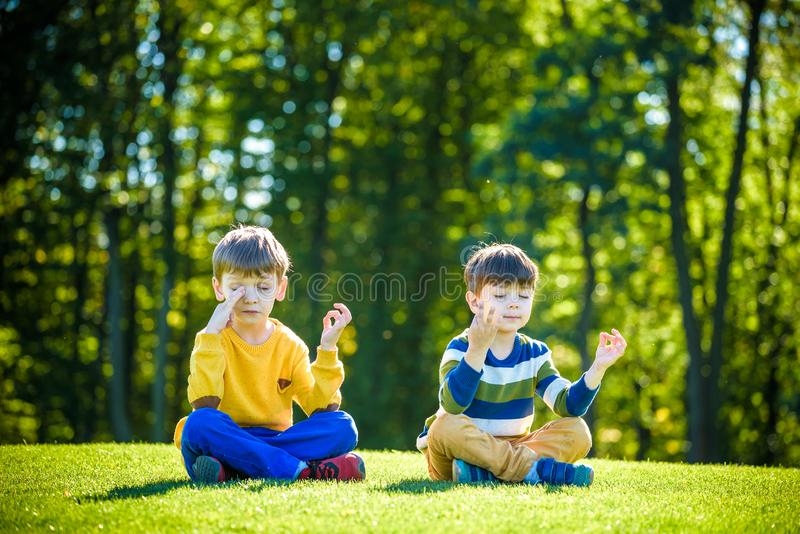 Två Caucasian pojkebrodervänner som ner sitter på nytt fält för grönt gräs och att göra meditation iklädd tillfällig kläder royaltyfria foton