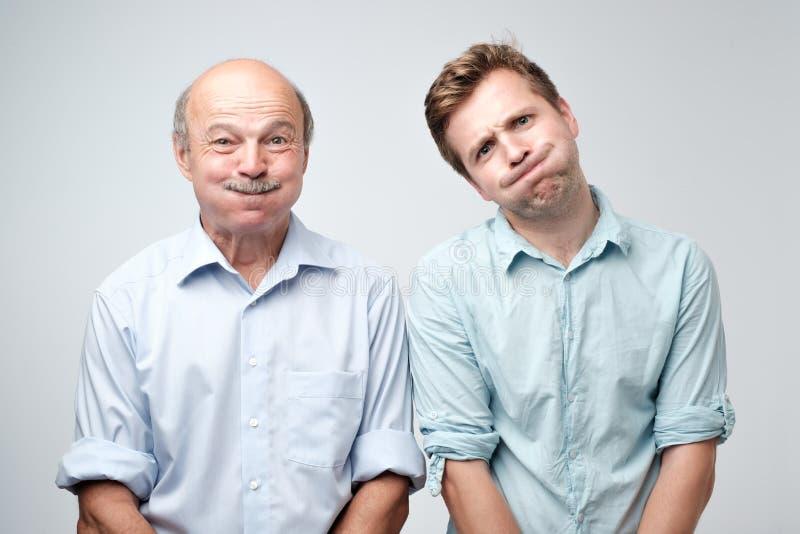 Två caucasian stiliga män som blåser kinder, medan kränkas på något som visar hans negativa sinnesrörelser arkivbilder
