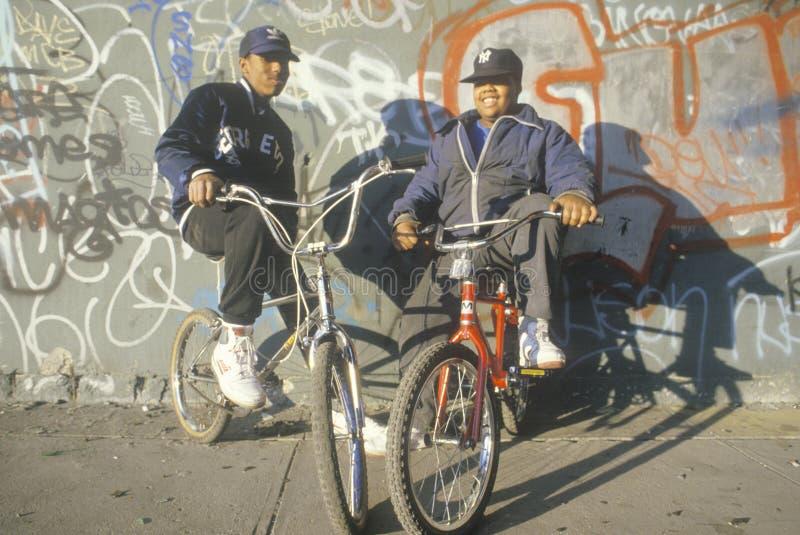 Två centrumafrikansk amerikantonåringar på cyklar, NY-stad royaltyfria bilder