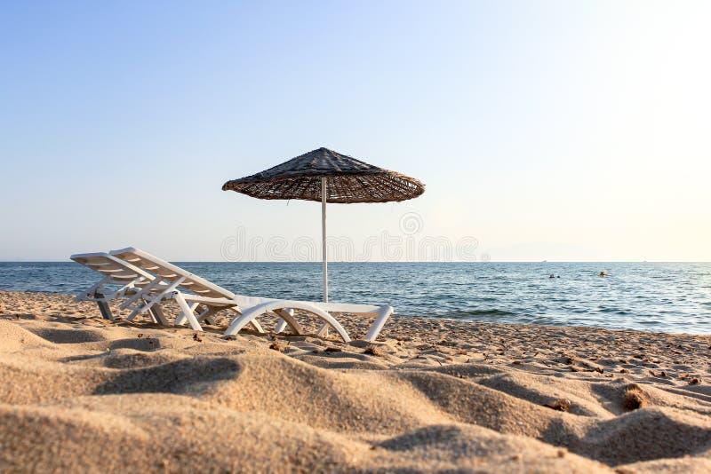 Två chaisevardagsrum och sugrörparaply på stranden arkivfoto