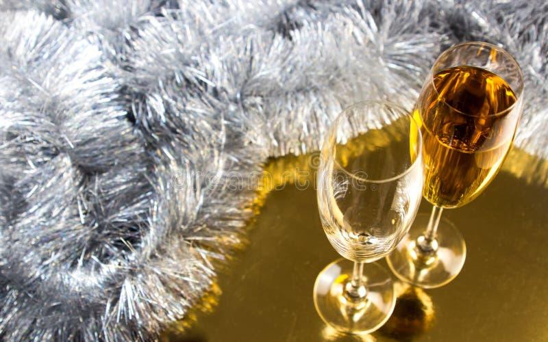 Två champagne- eller vinexponeringsglas med garnering för guld- och silverjulglitter arkivfoton