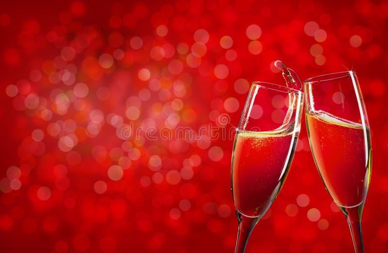 Två champagneexponeringsglas över röd julbakgrund royaltyfri foto