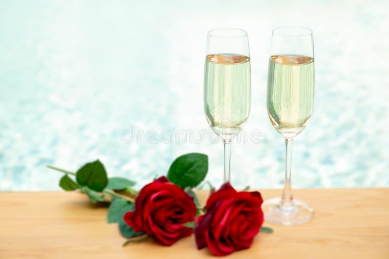 Två champagneexponeringsglas med den nästa simbassängen för rosa blomma arkivbilder