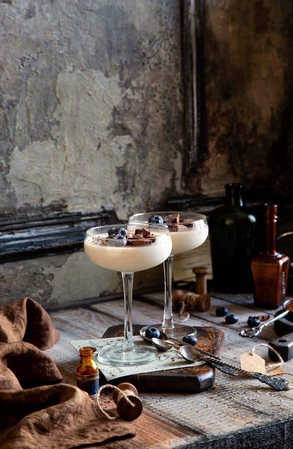 Två champagneexponeringsglas med karamell färgade pannacottaen, gelé, mousse, pudding med choklad och blåbär arkivbild