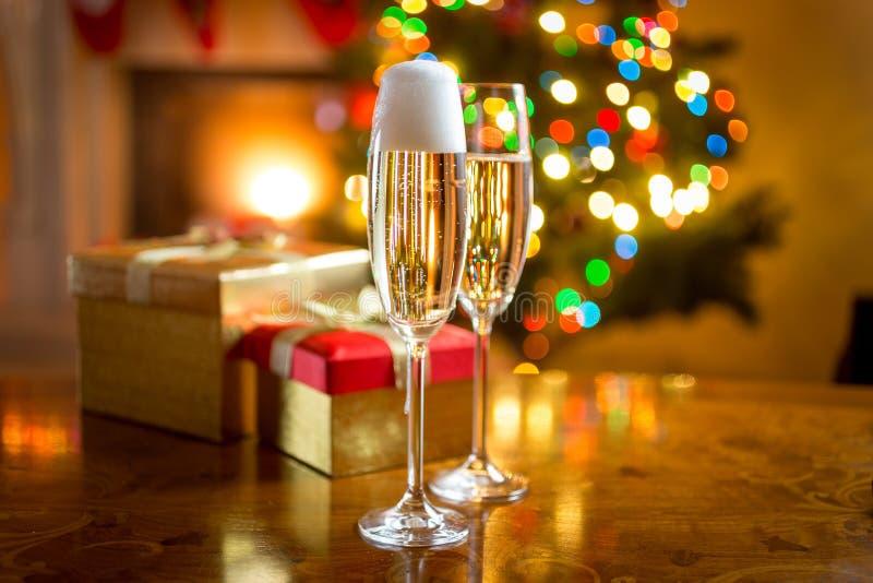 Två champagneexponeringsglas mot spisen som dekoreras för jul royaltyfria bilder