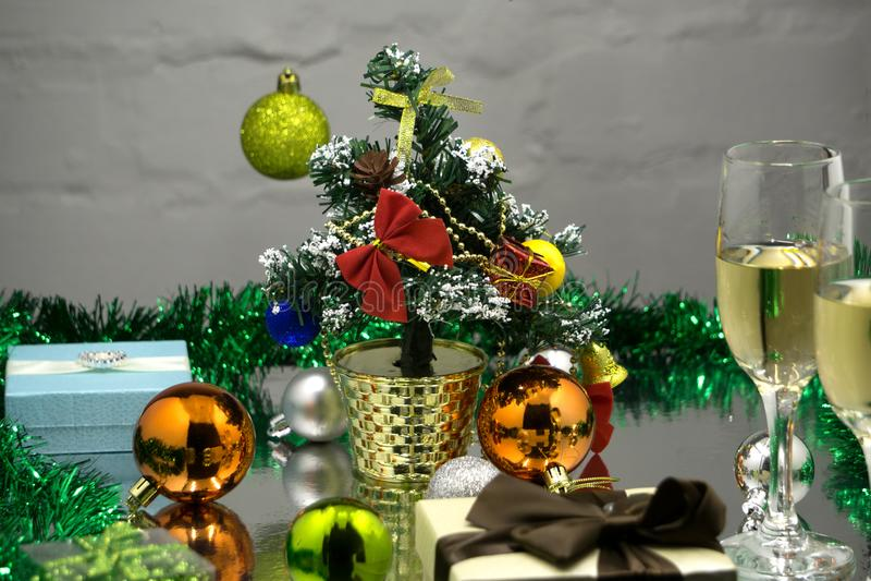 Två champagneexponeringsglas, röd boll för glad jul som hänger på granfilial under snö, och gran-kottar över färgrik suddig belys royaltyfria bilder