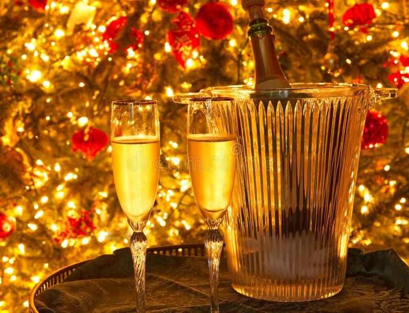 Två champagneflöjter och en champagneflaska i en exponeringsglasishink framme av en julgran arkivbild
