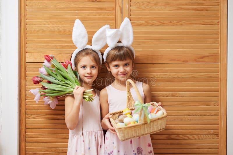 Två charma lilla systrar i klänningarna med vita kanins öron på deras huvud rymmer blommor och en korg med fotografering för bildbyråer