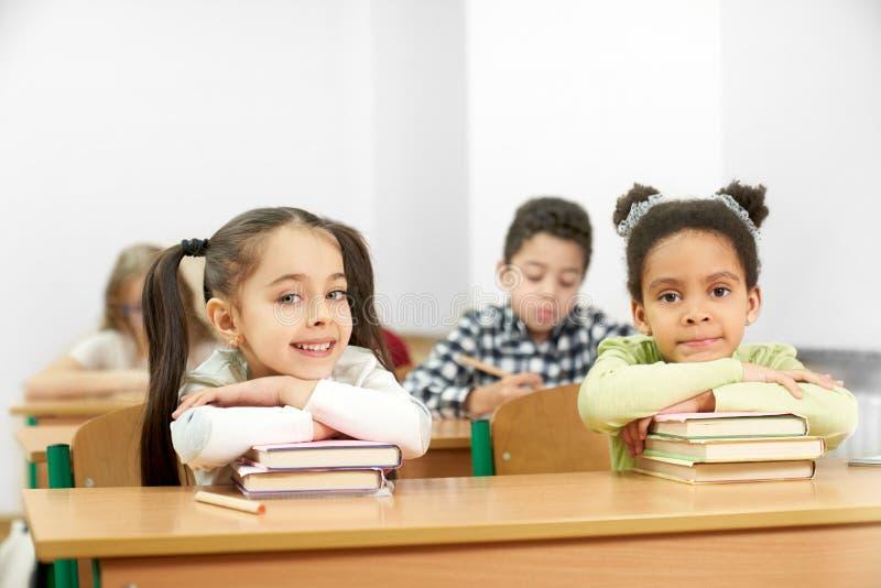 Två charma studenter som sitter på tabellen, i skola och att posera arkivfoton