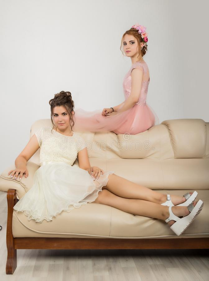 Två charma unga kvinnor i eleganta klänningar som sitter på en soffa, mjuk historia royaltyfria bilder