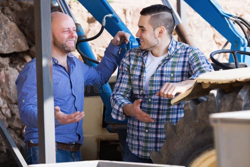 Två chaufförer som arbetar med traktoren royaltyfri foto