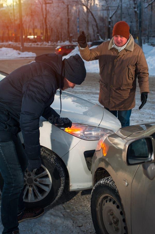 Två chaufförer som argumenterar efter bilkrasch på stadsgatan royaltyfri fotografi