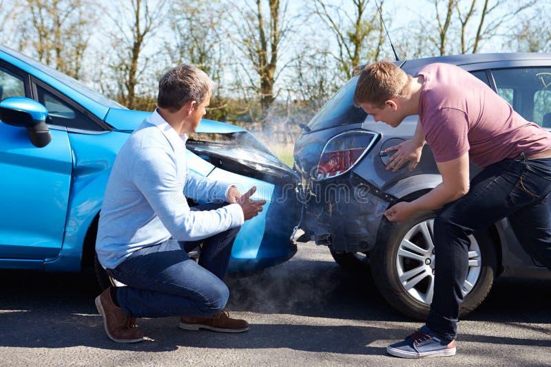 Två chaufförer som argumenterar efter trafikolycka royaltyfria bilder