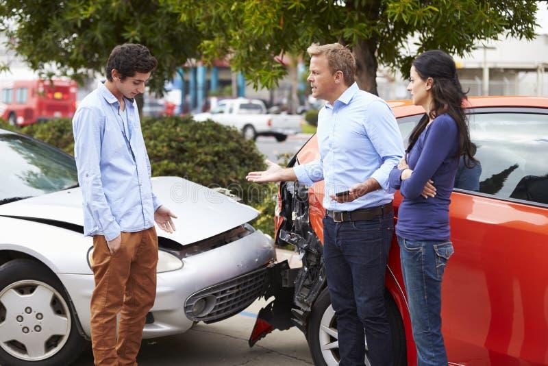 Två chaufförer som argumenterar efter trafikolycka royaltyfri foto