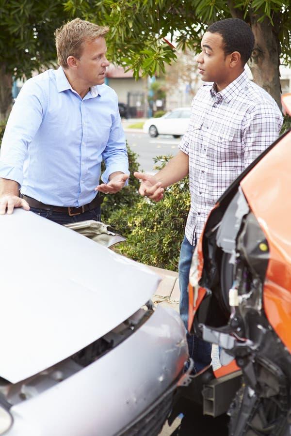 Två chaufförer som kontrollerar skada efter trafikolycka royaltyfri fotografi