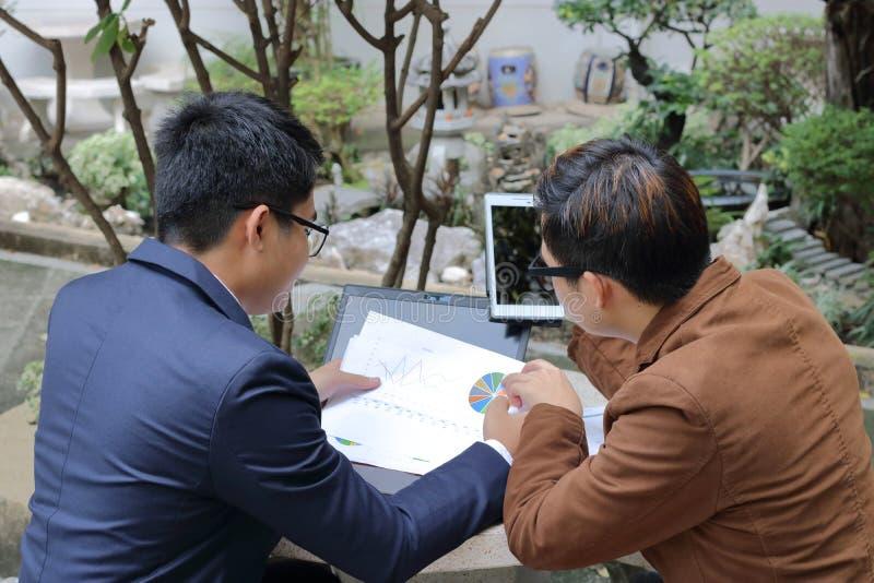 Två chefer diskuterar deras arbete i mötedag på offentligt utomhus arkivfoto