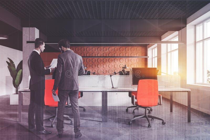 Två chefer i orange öppet utrymmekontor arkivbilder
