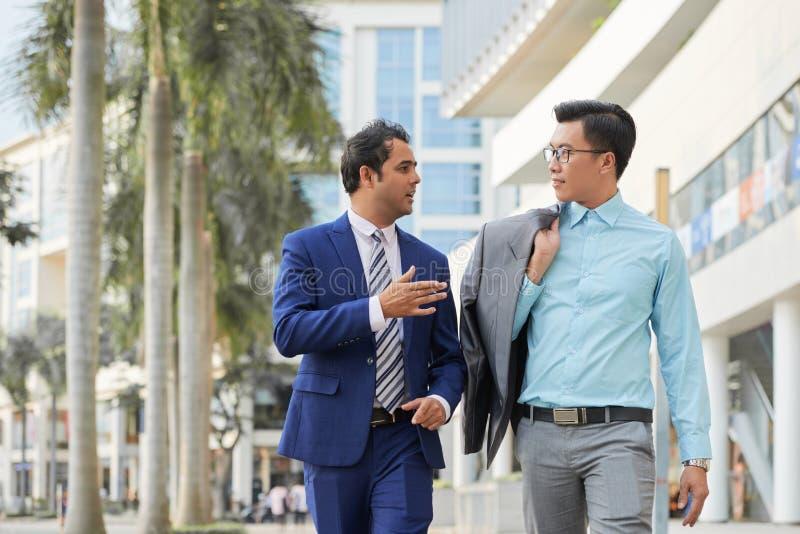 Två chefer som promenerar gatan i staden royaltyfria bilder