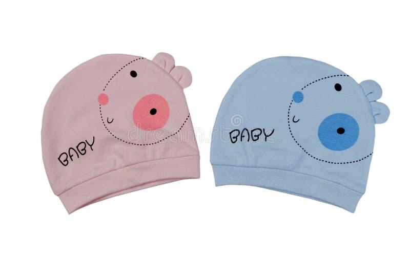 Två children& x27; s-hattar för kopplar samman, rosa färger och blått fotografering för bildbyråer
