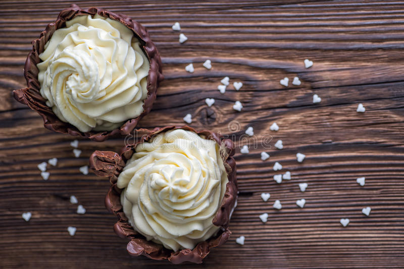 Två chokladefterrätter som fylls med vit, lagar mat med grädde på trätabellen, efterrätt med vita hjärtor för valentindag arkivfoton