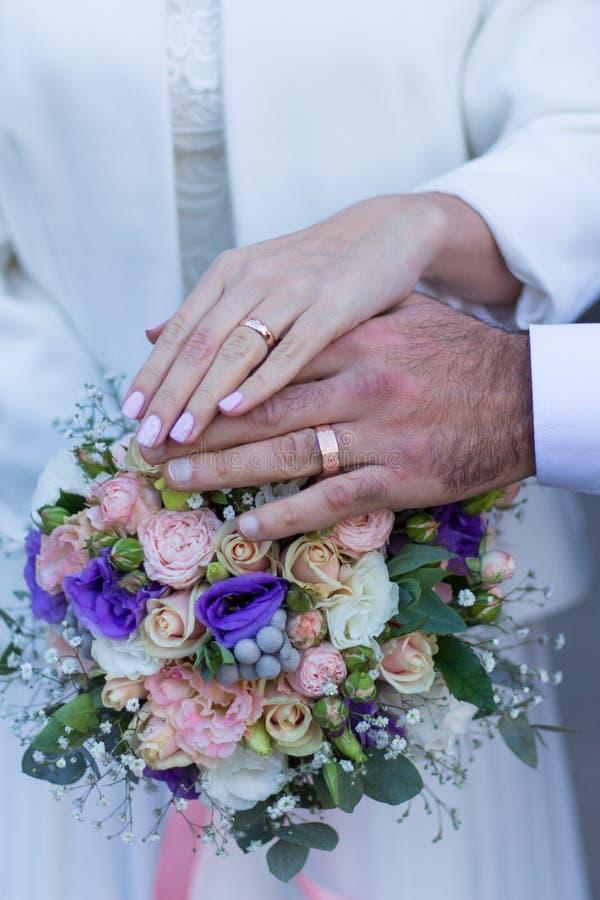 Två cirkel, två händer, bröllop- och kopplingsbukett royaltyfri bild