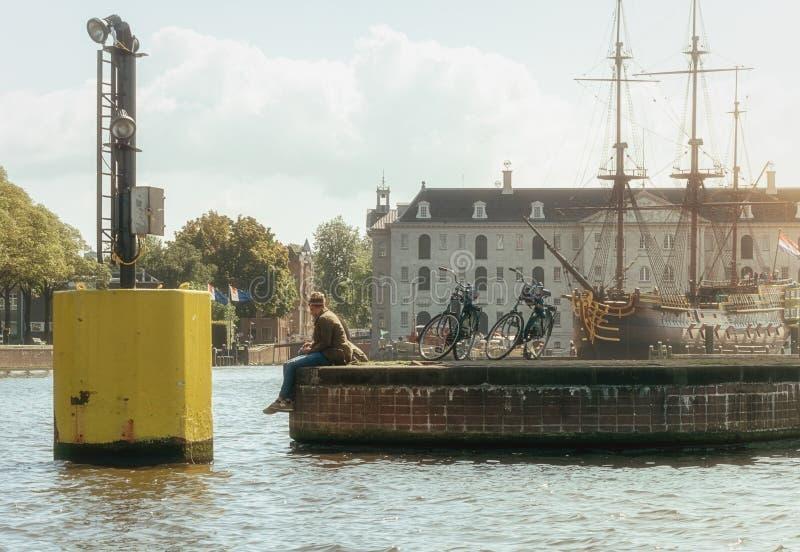 Två cyklister vilar på den Oosterdok kajen i Amsterdam royaltyfri bild