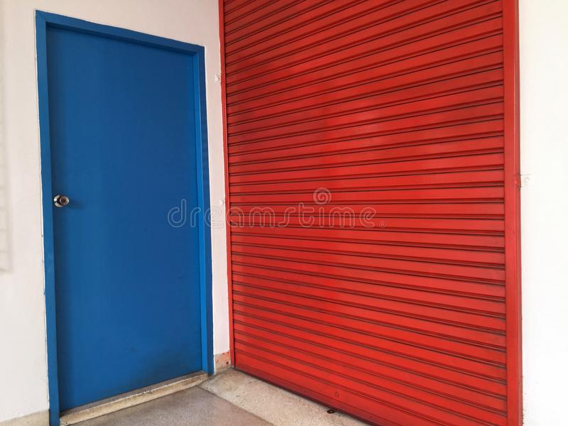 Två dörrar bredvid de, liten blå trädörr för att folk ska använda den stora röda metalldörren för stort material royaltyfri foto