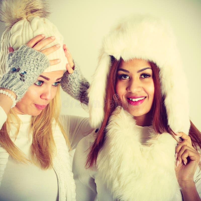 Två damer i den vita dräkten för vinter royaltyfria bilder