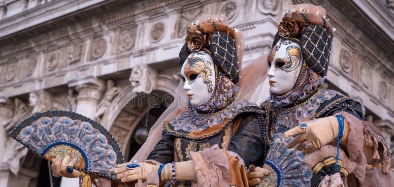Två damer i traditionell dräkt och maskeringar, med dekorerade fans som står av bågarna på St-fläckar, kvadrerar framme under Ven arkivfoto