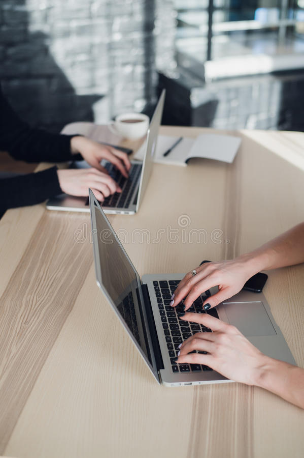 Två damer sitter på en tabell och skriver på bärbara datorer Stäng sig upp skottet av kvinnliga arbetare i regeringsställning som arkivfoton
