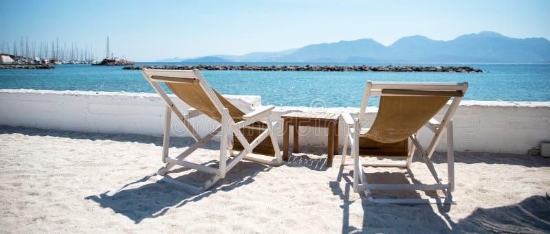 Två Deckchairs och soldagdrivare på stranden fotografering för bildbyråer