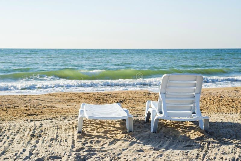 Två deckchairs på en strand som ut vänder mot till havet arkivfoto