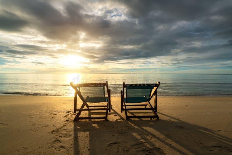 Två deckchairs på stranden på solnedgången med en tropisk havsbakgrund Lopp och semester i sommar på havet royaltyfri bild