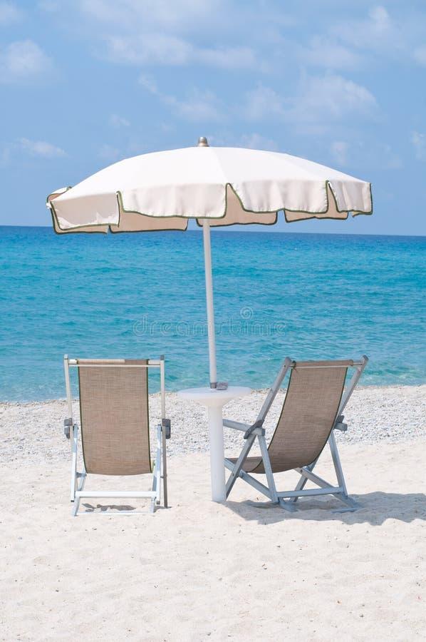 Två deckchairs på stranden under ett paraply arkivbild