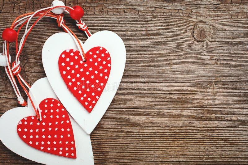 Två dekorativa röda och vita hjärta på en träbakgrund arkivfoton