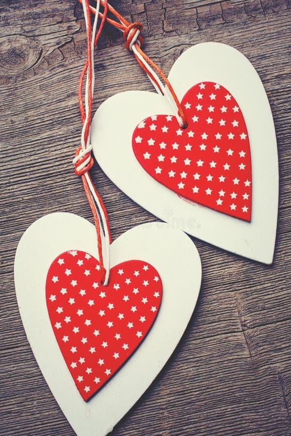 Två dekorativa röda och vita hjärta på en träbakgrund royaltyfri foto