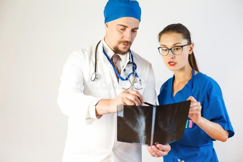 Två doktorer diskuterar en röntgenstråle Vit bakgrund royaltyfri fotografi