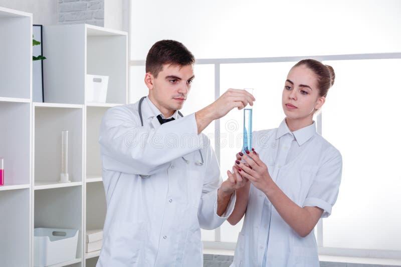 Två doktorer, en grabb och en flicka, i en vit kappa för medicinsk dressing, undersöker en genomskinlig flaska med en blå flytand arkivfoto