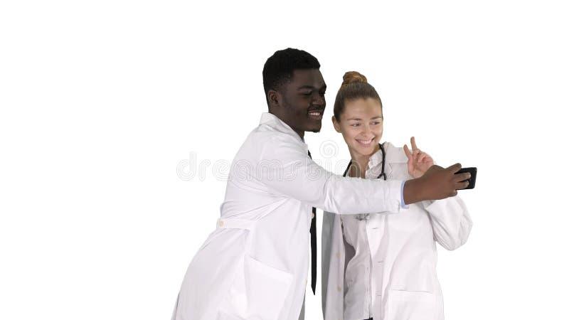 Två doktorer gör selfie genom att använda en smartphone och le på vit bakgrund royaltyfri fotografi