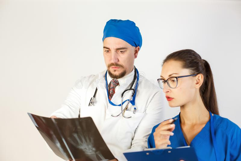 Två doktorer ser resultatet av en röntgenstråle, finns det ett problem, och de diskuterar behandlingen Vit bakgrund fotografering för bildbyråer
