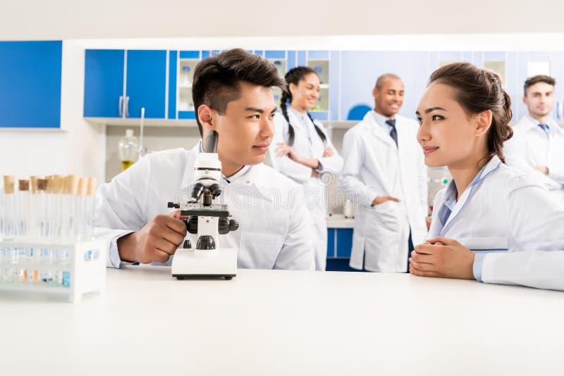 Två doktorer som arbetar med mikroskopet i laboratorium, medan deras kollegor är royaltyfria bilder
