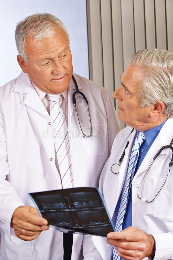 Två doktorer som diskuterar x-raxbild royaltyfri foto