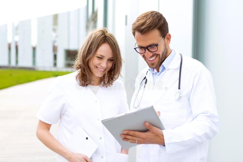 Två doktorer som framme arbetar av kliniken arkivfoton
