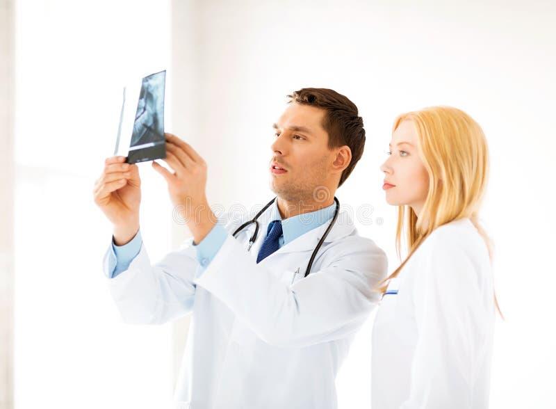 Två doktorer som ser röntgenstrålen royaltyfri fotografi